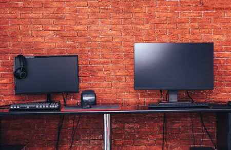 Two computer monitors with black screen on a desk, one workplace on table for two people.