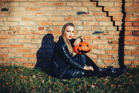 modern Halloween woman. Attractive witch holding pumpkin 'trick or treat'. Woman dressing in leather jacket and black skirt. October halloween. bricks background.