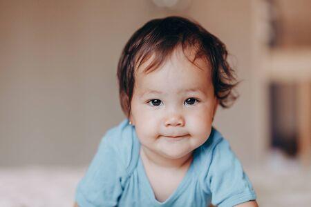 carina ridendo ragazza di un anno sdraiata sul letto e guardando la fotocamera tocca i suoi piedi. Archivio Fotografico