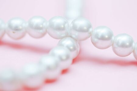 string of pearls delicate pink color, in soft focus, with highlights.