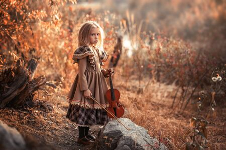 young violinist ,little girl in brovn vintage dress. Little girl holding the violin.portrait of a little girl with a violin.