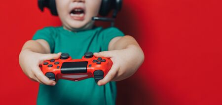 Little boy playing with red joystick have emotions on his face, shout, in headphones on red background.