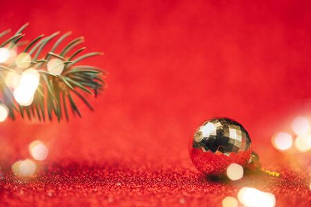Close up of disco ball with spruce branches on red background, selected focus, blurred red background.