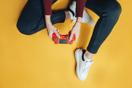 Young woman playing with gamepad on yellow.