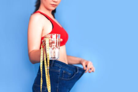 Woman holding water and measure tape 免版税图像
