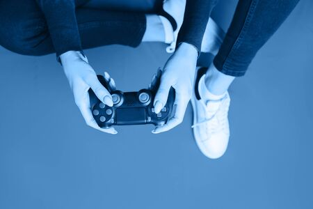 Young woman playing with gamepad on red.