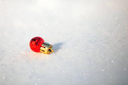 Red Christmas shinning ball lying on snow, ready christmas, sunset.