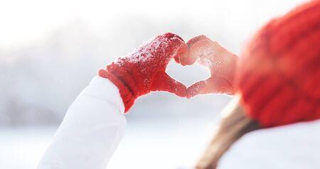 Femme faisant le symbole du coeur avec les mains enneigées Banque d'images