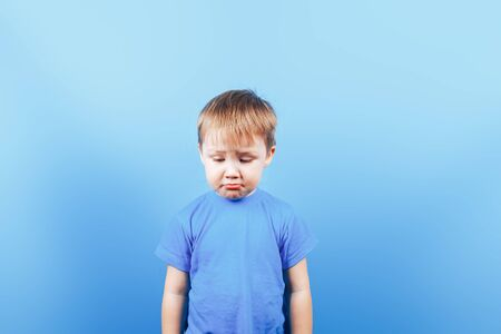 Upset crying sad boy at blue background