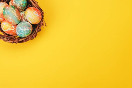 Coloeful easter eggs in nest on yellow color background.