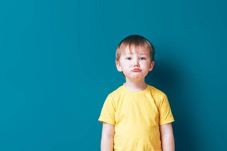 Upset crying sad boy at blue background Stock Photo