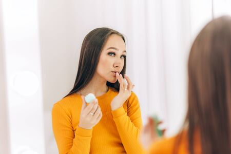 The girl doing makeup in front of the mirror