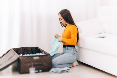 girl arrange clothes in the suitcase