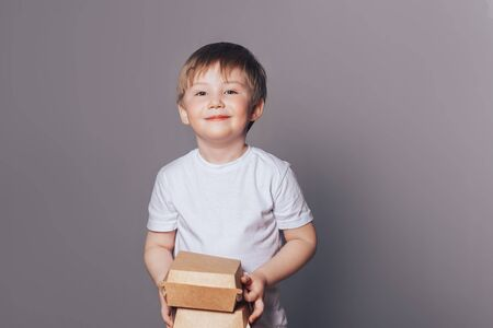 Beautiful little boy holding boxes in hands Banque d'images - 150442217