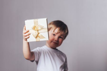 Beautiful little boy in a white T-shirt holding a gift in his hand Banque d'images - 150442228