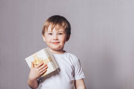 Beautiful little boy in a white T-shirt holding a gift in his hand Banque d'images - 150442229