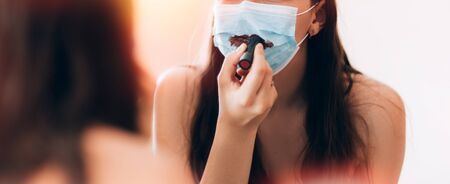 Young beautiful girl makes a make-up in medical mask Banque d'images - 150442236