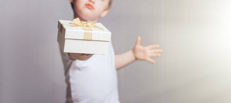 Beautiful little boy in a white T-shirt holding a gift in his hand Banque d'images - 150442239