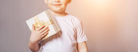 Beautiful little boy in a white T-shirt holding a gift in his hand, mother's day, Valentine's day, March 8, birthday, long banner