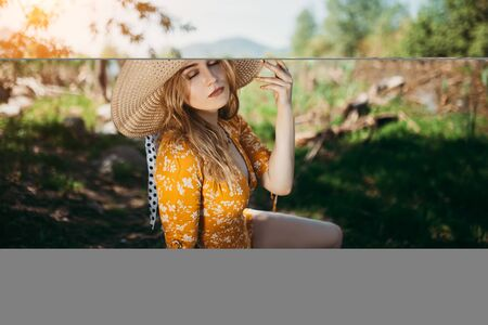 Young beautiful girl in beautiful yellow dress and hat sitting on green lawn in the open air