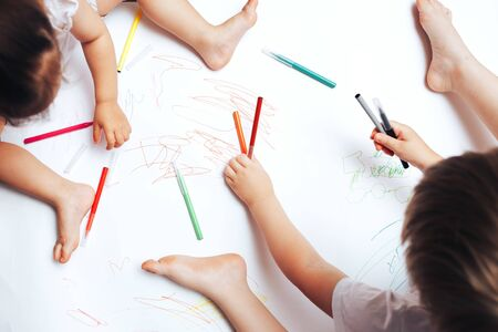Talented children draw with colored felt-tip pens on white paper, lessons, tasks with children of the different ages. flat lay, top view