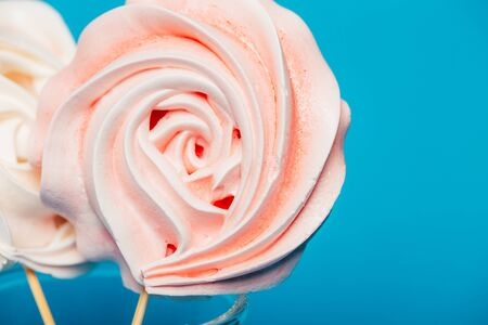 Beautiful tender meringue on a stick in a glass on a blue background, March 8, Mom day, birthday present, sweets.