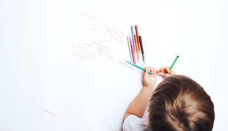 Little child draws on white paper with colored felt-tip pens, teaching children to draw.