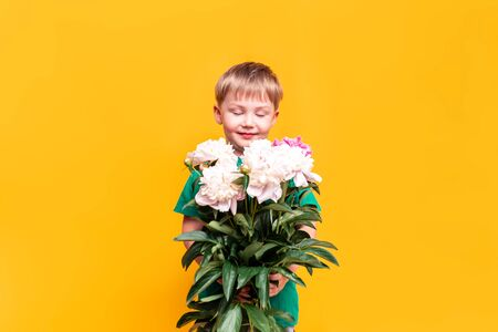 Little boy holding a bouquet of beautiful flowers in his hands, mothers day, March 8, fathers day