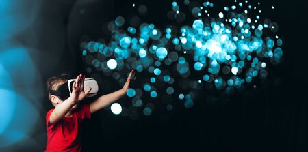 Small Boy experiencing virtual reality on black background with light luminous effects