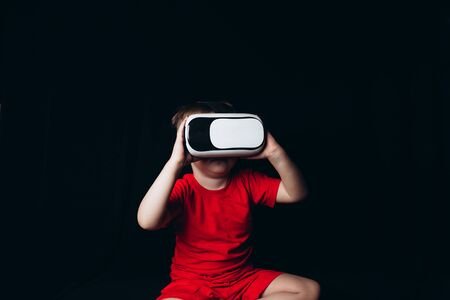 Small Boy experiencing virtual reality on black background with light luminous effects Banque d'images - 150099310