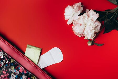 sanitary napkin stick out from the bag and in the corner are beautiful peonies on a red background, health care, monthly protection, reliable friend