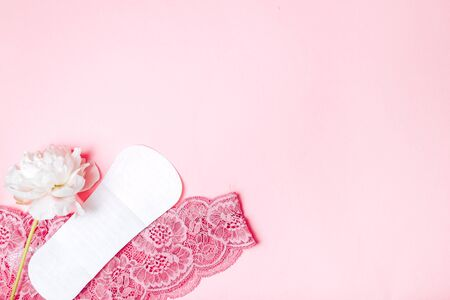 sanitary napkin with a beautiful peony and underwear on a pink background, health care, monthly protection, reliable friend