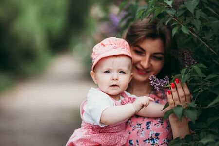Young beautiful mother with small child in pink clothes on the background of beautiful blooming lilac in the open