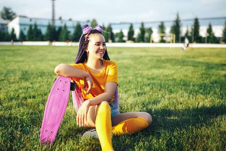 Young beautiful girl sitting on a lawn holding a skateboard in her hand in a yellow T-shirt and yellow socks in the open