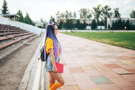 Young beautiful girl holding a red folder in her hand in a yellow T-shirt walking in the open air at a sports stadium. Student girl back to school Banque d'images