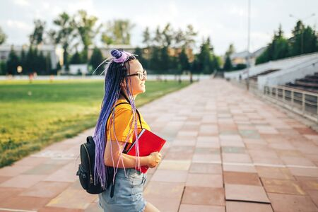 Young beautiful girl holding a red folder in her hand in a yellow T-shirt walking in the open air at a sports stadium Student girl back to school Banque d'images