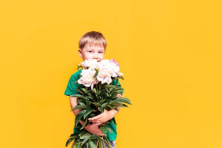 Little boy holding a bouquet of beautiful flowers in his hands, mothers day, March 8, fathers day Banque d'images - 150014711