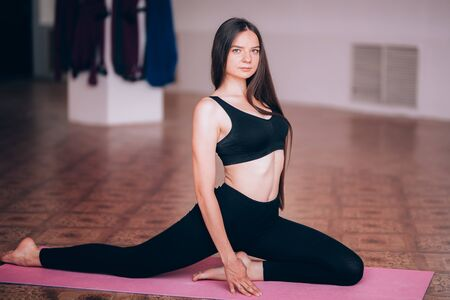 Beautiful young girl does hatha yoga on the mat, relaxes, taking care of health Banque d'images