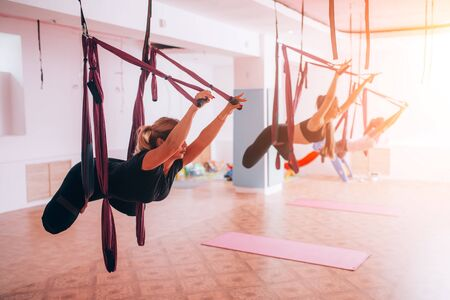 Beautiful young girls doing fly yoga on hammocks, healthy lifestyle Banque d'images - 150014717