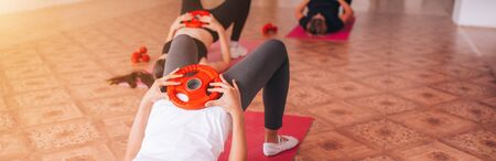 Beautiful young girls do fitness on mats, relax, care about health. Banque d'images - 150099348
