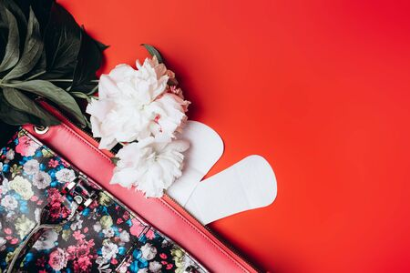 sanitary napkin stick out from the bag and in the corner are beautiful peonies on a red background, health care, monthly protection, reliable friend. Archivio Fotografico