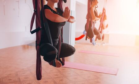 Beautiful young girls doing fly yoga on hammocks, healthy lifestyle. Banque d'images - 150099589