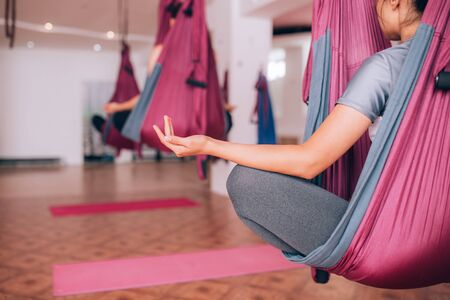 Beautiful young girls doing fly yoga on hammocks, meditating on hammocks, health care. Banque d'images - 150099603
