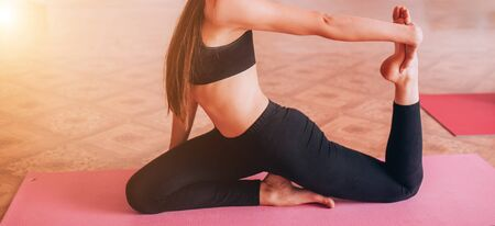 Beautiful young girl does hatha yoga on the mat, relaxes, taking care of health.