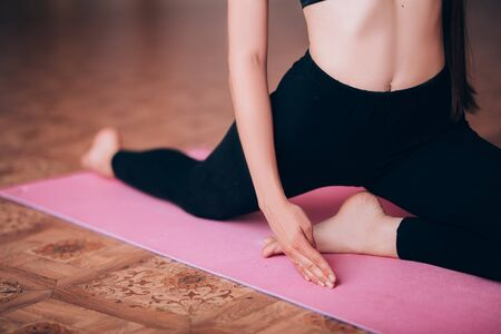 Beautiful young girl does hatha yoga on the mat, relaxes, taking care of health. Banque d'images - 150374224