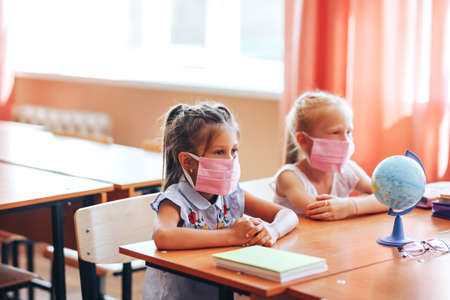 Two little schoolgirls sit at a desk in a school class in medical masks and carefully listen to the teacher. Banque d'images