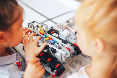 Two schoolgirls study in a robotics class, assemble a robot constructor.