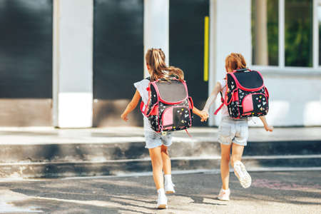 Two schoolgirls holding each other's hands run to school, back to school, primary education of children.