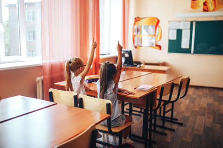 Two little schoolgirls sit at a desk in a school class and raise their hands..