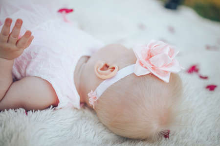 Little newborn baby in a pink dress on a white plaid in a park. Banque d'images